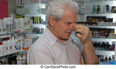 Male customer feels bad at the drugstore - Senior male...