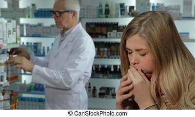 Woman caughs at the drugstore - Pretty blond woman caughing...