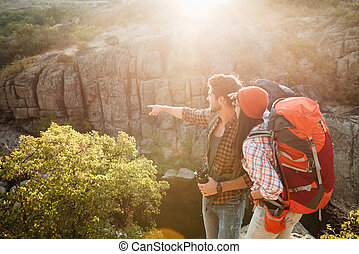 Adventure couple stands sideways near the canyon. man shows...