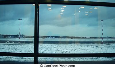 Unrecognizable passengers at the airport against window to airfield. Tourism, travel, waiting concepts. 4K steadicam video