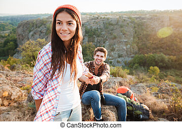 Young traveler couple in the mountains. girl holding man....