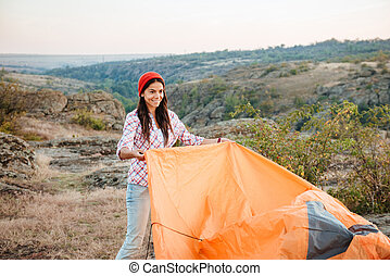 Young girl collect tent - Young gril collect tent on...