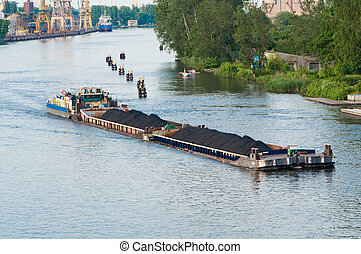 coal barge sailing on the river with cargo