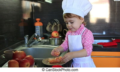 cute little baby dressed as a cook helps mum in the kitchen...