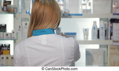 Female pharmacist turns around at the drugstore - Attractive...