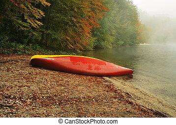 boat on bank of river in autumn