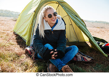 Woman in sunglasses and boots sitting near tent at campsite...
