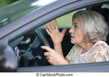 senior woman driving car - portrait of stressed senior woman...
