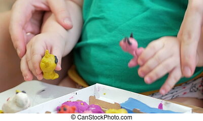 Beautiful baby boy sculpts the clay with his mother at home....