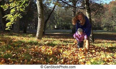 Young mother and her toddler girl have fun in autumn nature. 4K
