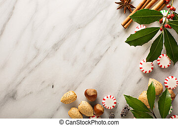 Holiday background with peppermint candy, nuts and spices on...