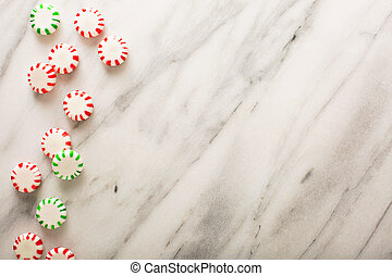 Holiday background with peppermint candy on marble