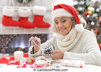 Senior woman in Santa hat - Portrait of smiling senior woman...