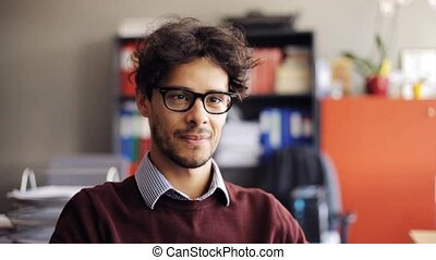 smiling young man in eyeglasses at office