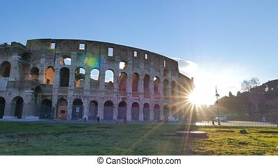 The sun comes out from behind the Coliseum. Rome, Italy....