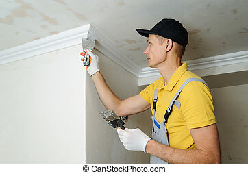 Installation of ceiling moldings. Worker puts glue on...