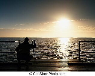 Professional photograph at sea. Tourist on wharf photograph...