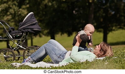 Happy mother with her young son on the hands played, lying on green grass. Gentle embrace.