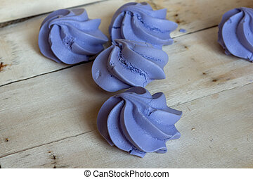 French blue meringue cookies on white wooden background