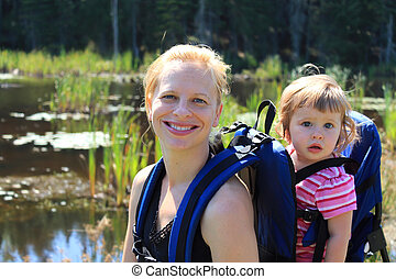 Mother and daughter hiking - Pretty blonde woman carrying...
