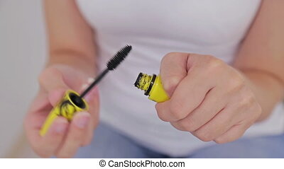 Beautiful young woman opening and putting mascara - Two...