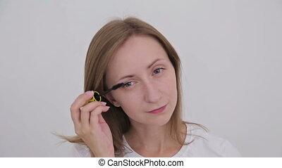 Beautiful young woman putting mascara and looking at camera....