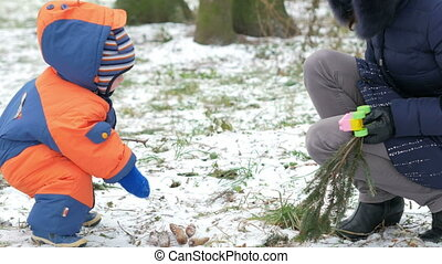 Attractive baby playing in the winter woods with her mother....