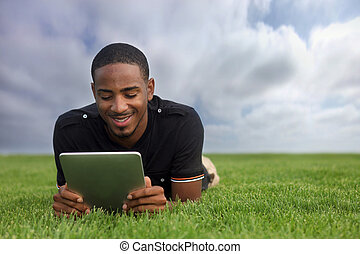 African American Student Reading Outdoors - College Student...