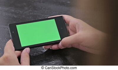 Woman using smartphone with green screen and scrolling....