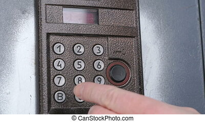 Person dialing number of apartment on a doorphone