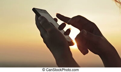 Woman hands with smartphone at sunset