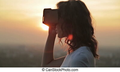 Woman uses a virtual reality glasses at sunset