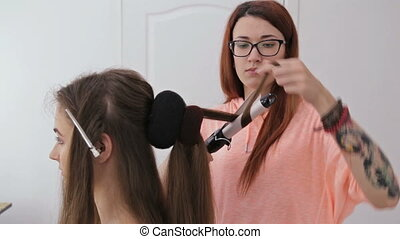 2 shots. Professional hairdresser doing hairstyle for young pretty woman