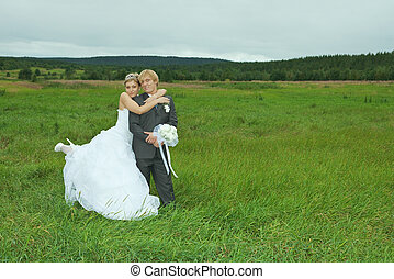Bride and groom embrace on field - The bride and groom...