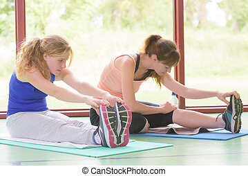 Ladies reaching for their toes during exercise routine
