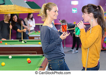Women in pool hall with drinks