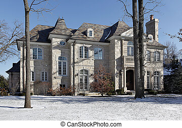Luxury stone home in winter with front balcony