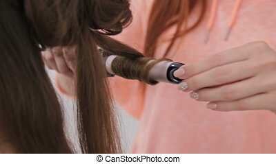 Close up shot. Hairdresser doing hairstyle for young pretty...