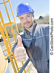 happy construction worker gesturing thumbs up outdoors