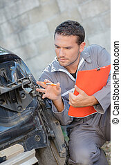 Mechanic making an assessment of a damaged car