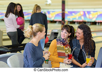 Women with drinks at bowling alley
