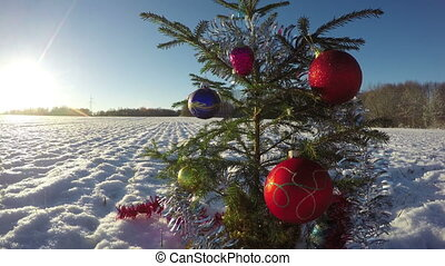 Beautiful Christmas tree with bauble on snowy field, time...