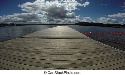 Footbridge into resort lake with on sunny summer day, 4K