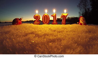 Happy New Year 2017 - beautiful candles on snow in garden, time lapse 4K