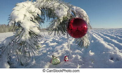 Snowy New Year pine branch with Christmas bauble on field,...