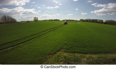 tractor spraying young wheat field, 4 K - Agriculture...