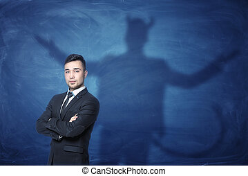 Businessman standing with hands across and his shadow on...