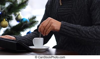 Cup with hot coffee on grey Table. Christmas lights background