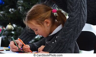 Father helping her daughter in drawing. Watching little girl drawing on paper. Christmas lights background