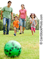 Family playing football in the park - Kids run towards the...